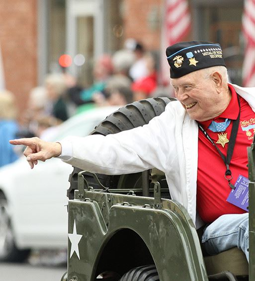 veteran waving in a parade